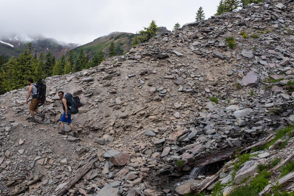 Dos personas escalando una montaña rocosa