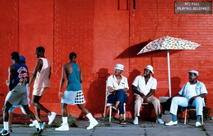 3 hombres negros sentados mirando a otros 3 en un dia de verano
