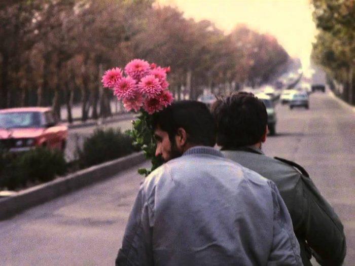 Sabzian en una motocicleta con otro hombre, cargando unas flores