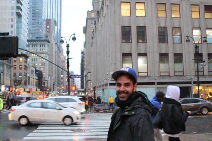Hombre sonriendo al cruzar una calle