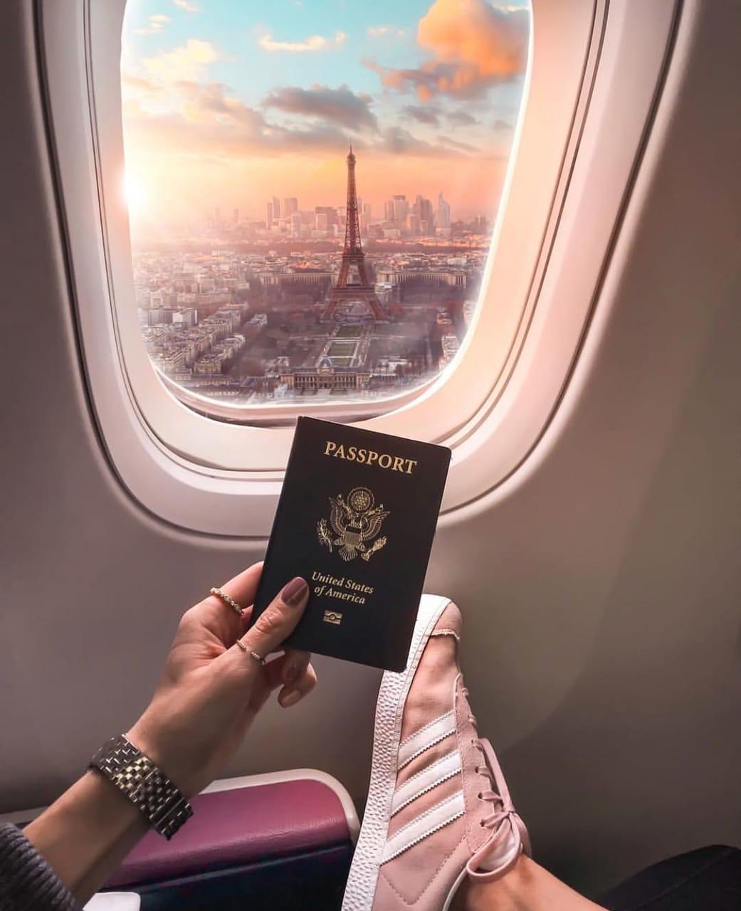 mujer en un avión, mostrando su pasaporte con la Torre Eiffel de fondo