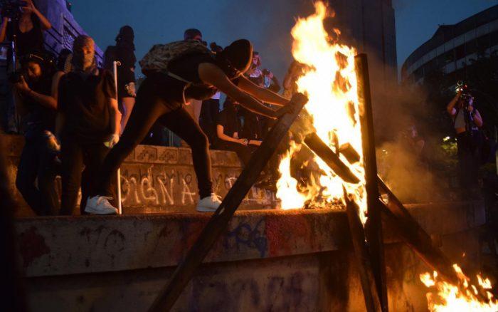 Mujeres encapuchadas encendiendo un fuego