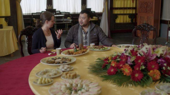 david chang hablando con una mujer en una gran mesa circular con muchos platillos