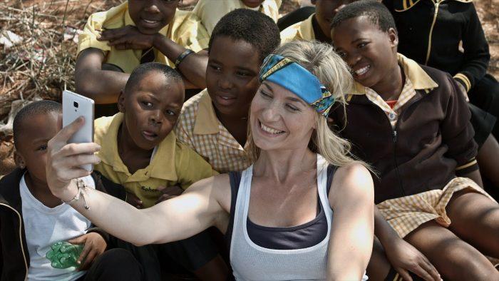 mujer blanca tomandose una selfie con mucho niños africanos