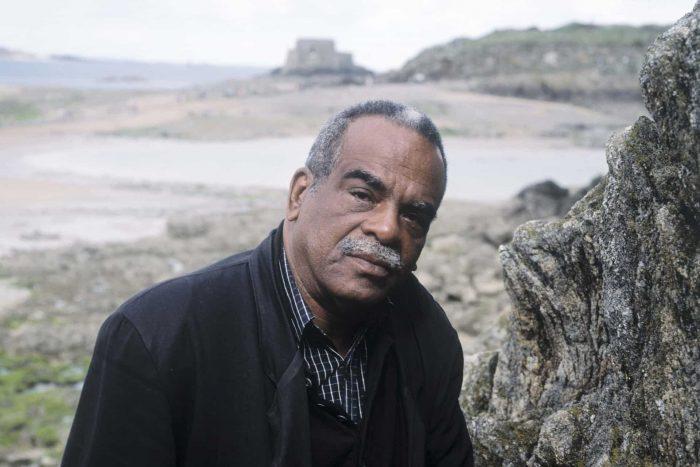 Fotografía de un hombre negro en una playa rocosa, con un bigote y pelo canosos