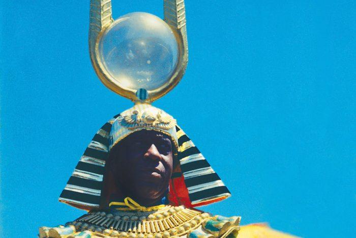 Hombre negro con un traje egipcio y un casco con una gran antena con una bola de cristal
